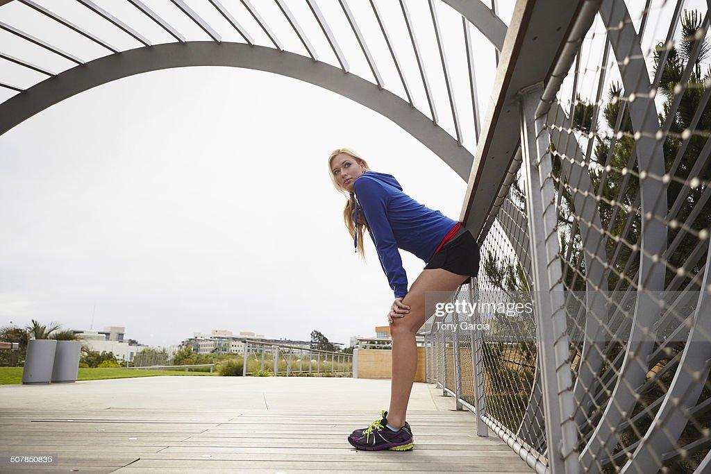Woman resting against fence, Tongva Park, Santa Monica, California, USA