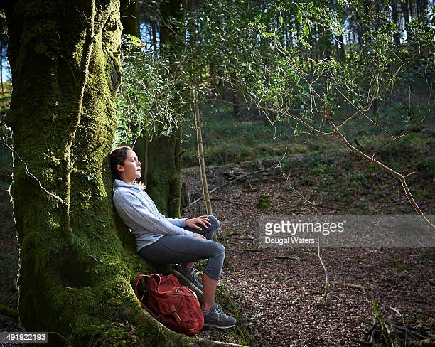 Woman resting against tree trunk in forest.