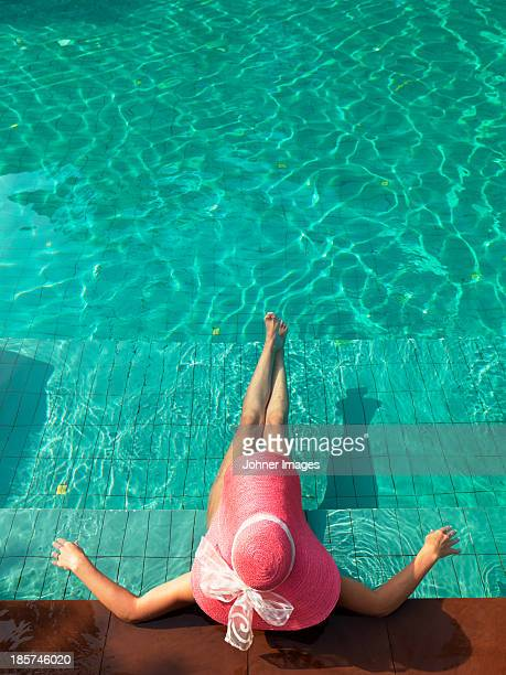 Woman resting at edge of swimming pool