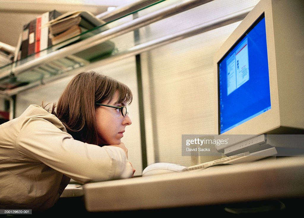 Woman resting head on arms, looking at computer monitor in office : Stock Photo