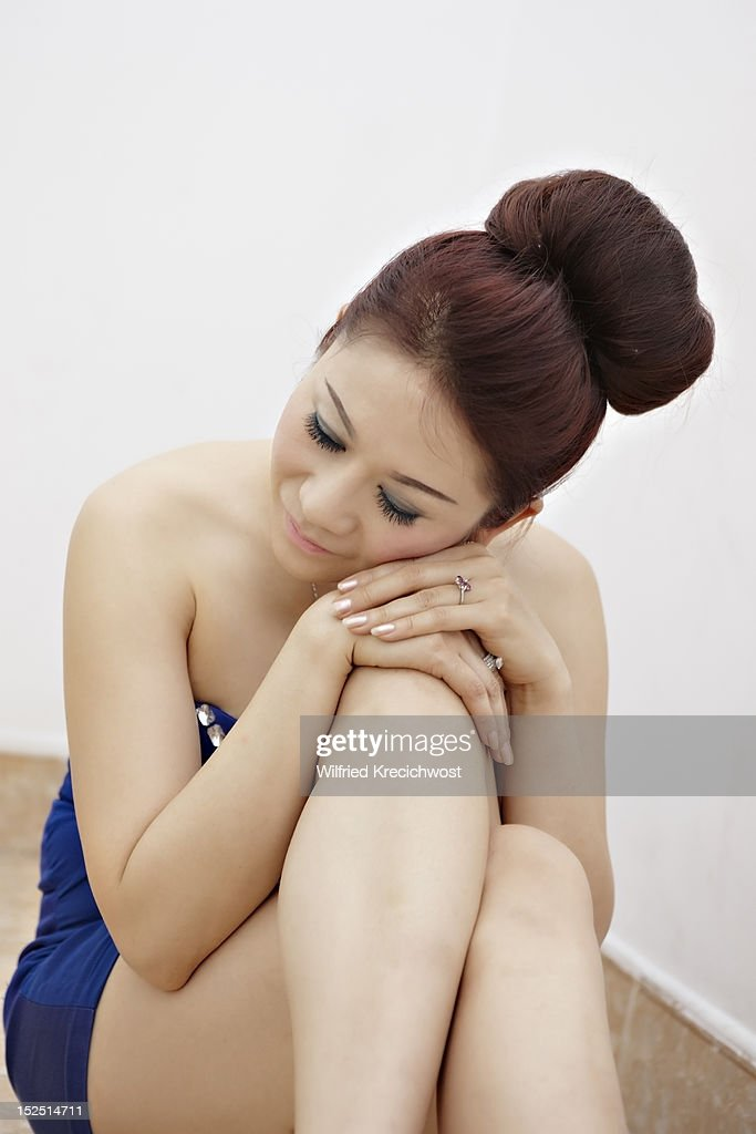A woman resting her head on her knee : Stock Photo