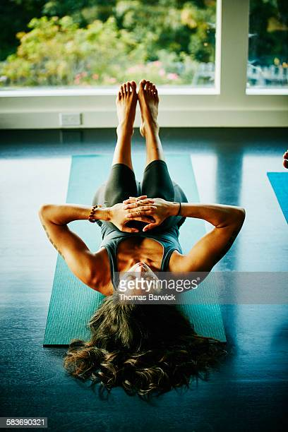 Woman resting in knee pose after yoga class