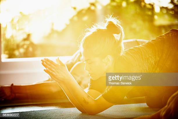 Woman resting in prayer position during yoga class