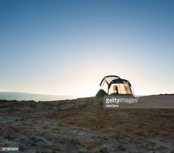 Woman resting in translucent tent camped on wild beach