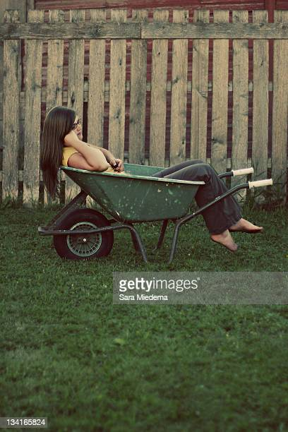 Woman resting in wheelbarrow