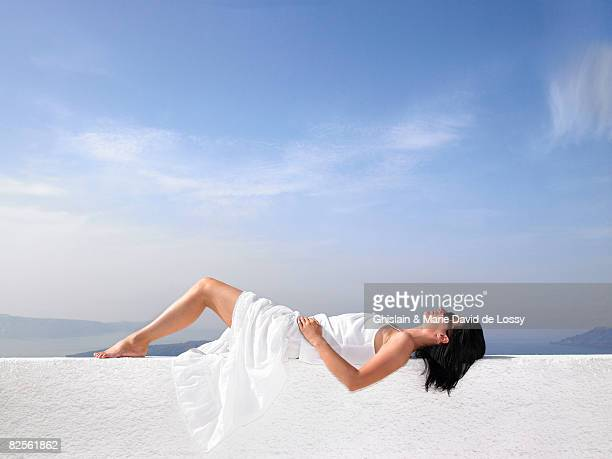 Woman resting on a white wall