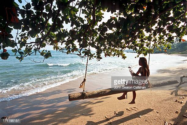Woman resting on beach swing.