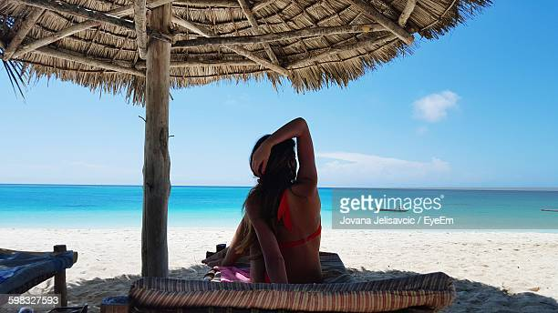 Woman Resting On Bed Below Thatched Roof Parasol At Beach