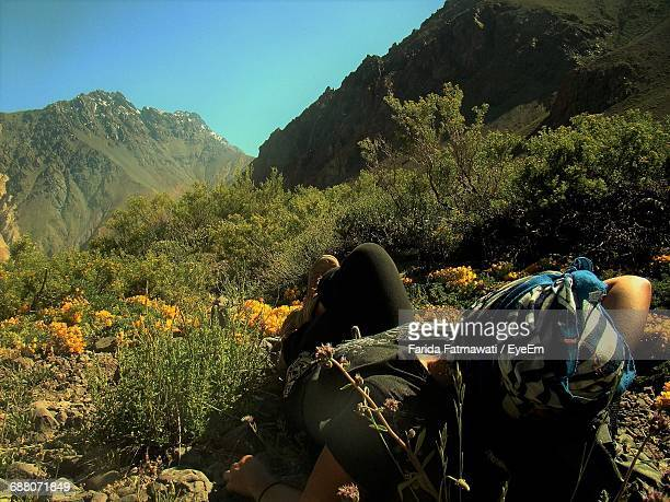 Woman Resting On Field By Mountains Against Sky
