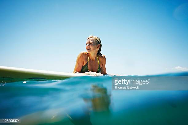 Woman resting on surfboard in water smiling