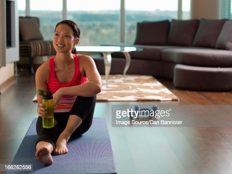 Woman resting on yoga mat in living room