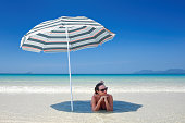 Woman on a desert tropical beach relax in the sunny day under a umbrella. Travel background .