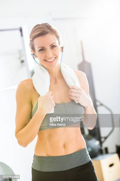 Woman resting with towel around neck in gymnasium