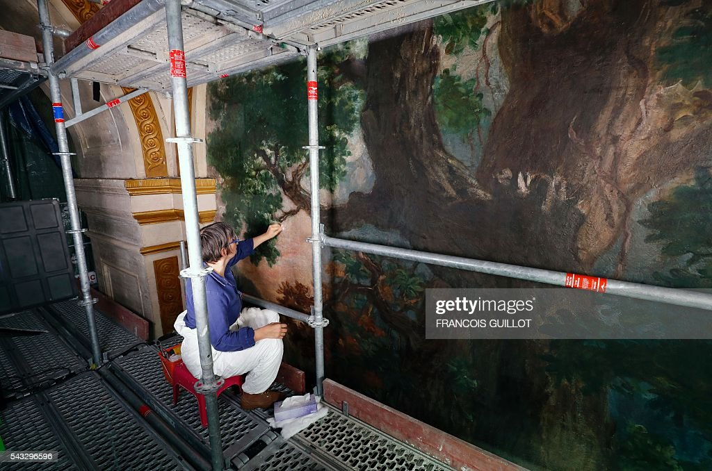 A woman restores the Eugene Delacroix paintings made between 1849 and 1861 at the Saints-Anges chapel inside the Saint-Sulpice church in Paris, on June 27, 2016. / AFP / FRANCOIS