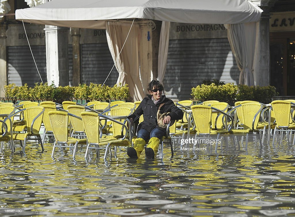 A woman rests at the table in Saint Mark's Square during today's Acqua Alta on November 5, 2013 in Venice, Italy. The high tide, or acqua alta as it is locally known, is a natural event most commonly affecting the city during Autumn and Winter.