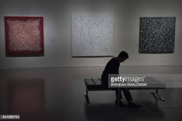 A woman rests during a preview of the Yayoi Kusama's Infinity Mirrors exhibit at the Hirshhorn Museum February 21 2017 in Washington DC Kusama has...