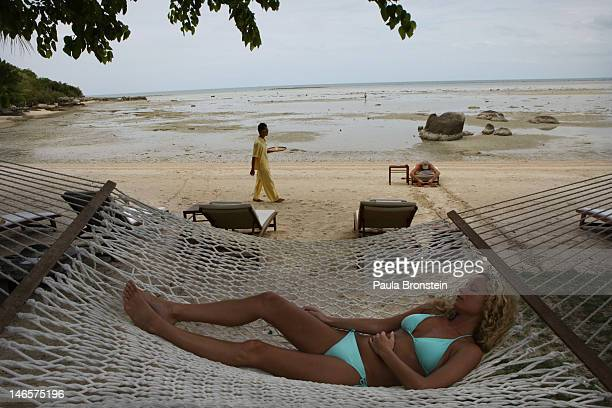 A woman rests on a hammock at the beach at the Kamalaya Wellness Sanctuary June 18 2012 Thailand's official tourism body the Tourism Authority of...
