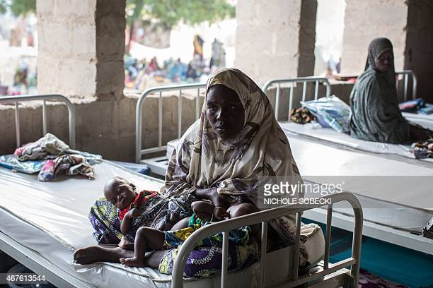A woman rests with her twin infants in a makeshift maternity ward in Maiduguri on March 25 2015 Nigeria's military has retaken the northeastern town...