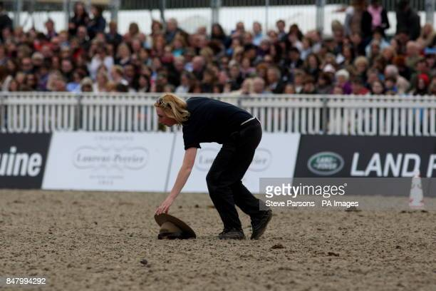 A woman retrieves a Mountie's hat which escapes being trampled The Royal Canadian Mounted Police perform for Queen Elizabeth II at the Royal Windsor...