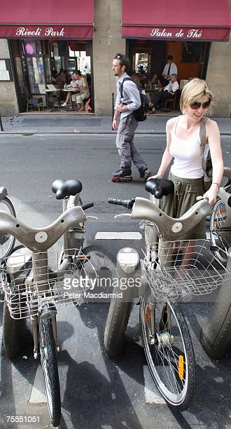 A woman returns a 'Velib' rental bicycle after using it in central Paris on July 19 2007 The new scheme uses 20000 heavy duty bicycles which can be...