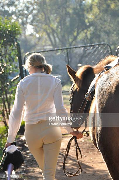 Woman rider leads horse to gate