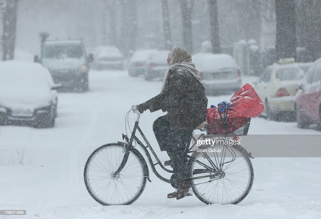 A woman rides a bicycle across a snow-covered street during a heavy snowfall in Zehlendorf district on December 9, 2012 in Berlin, Germany. Northeastern Germany was inundated with snow that covered highways and blanketed the region.