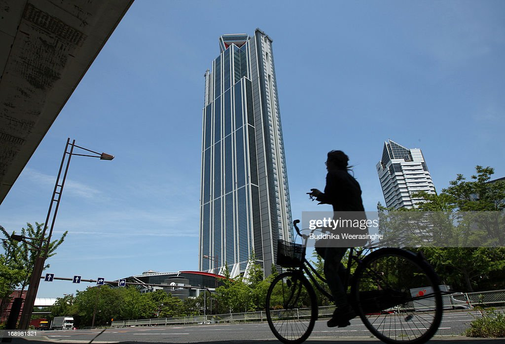 A woman rides a bicycle beside commercial buildings on May 17, 2013 in Osaka, Japan. Japan's economy recently shows the sign of recovery as the growth of last quarter was 0.9 percent, or 3.5 percent on annual basis.