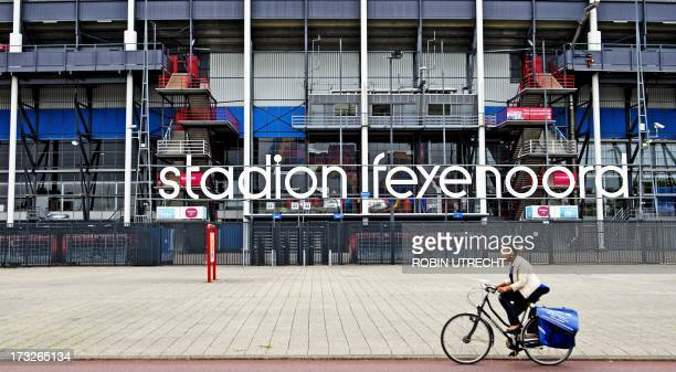A woman rides a bicycle in front of De Kuip Feyenoord football stadium in Rotterdam on July 11 2013 Leefbaar Rotterdam the largest opposition party...