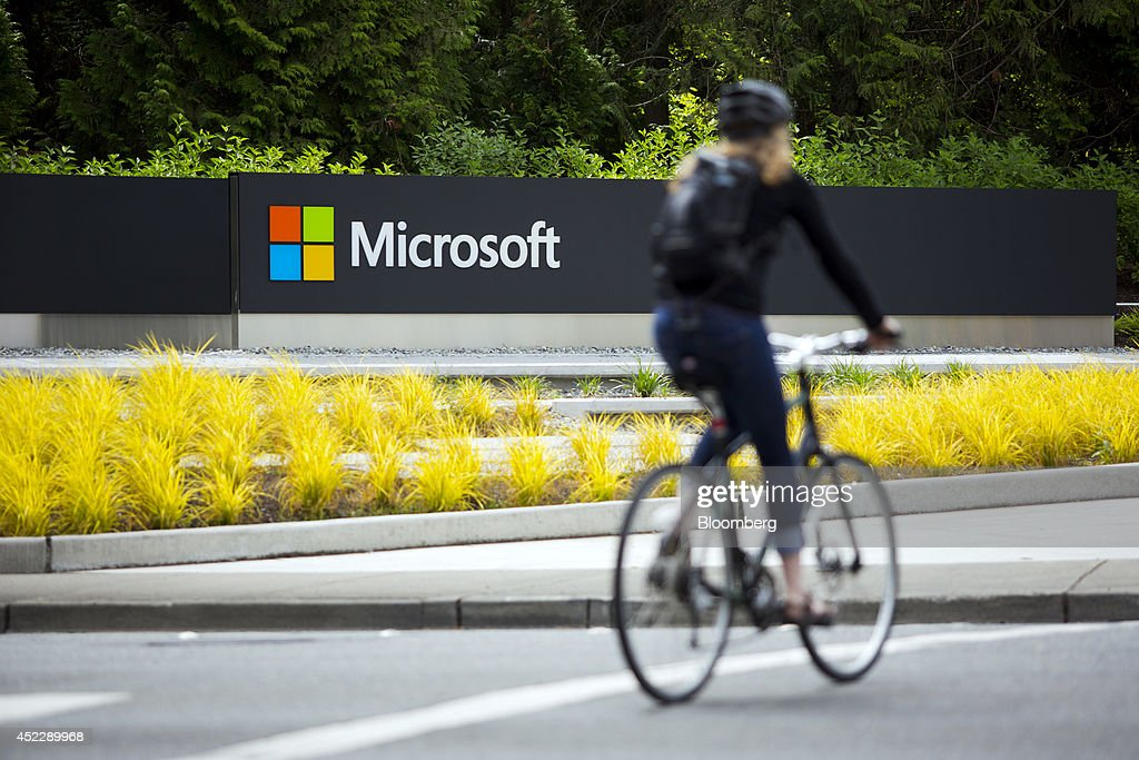 A woman rides a bicycle past a Microsoft Corp sign on the company's main campus in Redmond Washington US on Wednesday July 17 2014 Microsoft Corp...