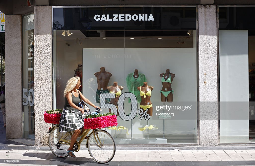 A woman rides a bicycle past a store advertising a half price sale on swimwear and beach clothes in Pescara, Italy, on Thursday, Aug. 29, 2013. Italian consumer confidence rose this month more than economists expected as households grew optimistic amid expectations that the government would cut a property tax. Photographer: Marc Hill/Bloomberg via Getty Images