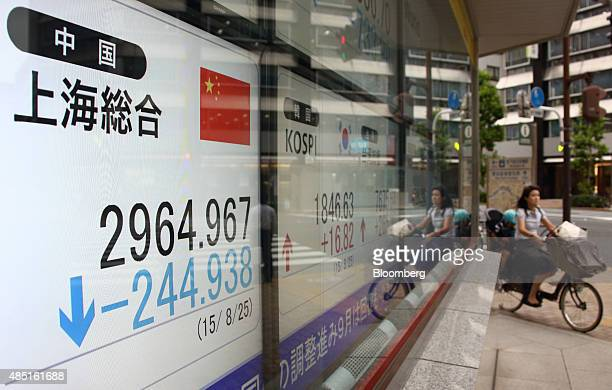A woman rides a bicycle past an electronic stock board displaying the Shanghai Composite Index outside a securities firm in Tokyo Japan on Tuesday...
