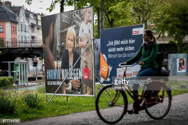 A woman rides a bicycle past election campaign billboards of the German Social Democrats and the German Christian Democrats ahead of state elections...