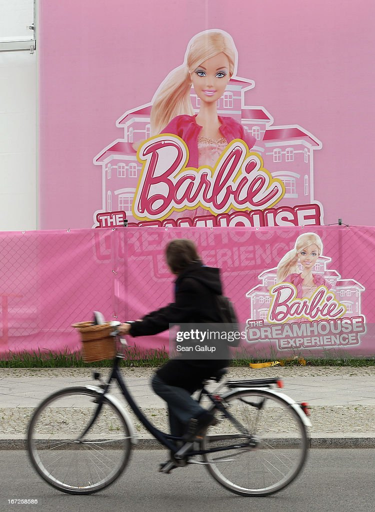 A woman rides a bicycle past the construction site of the Barbie Dreamhouse Experience on April 23, 2013 in Berlin, Germany. The Barbie Dreamhouse Experience is a 2,500 square meter structure meant to show Barbie's ideal house in life scale and will offer interactive tours and other experiences. The house is scheduled to open to the public on May 16.