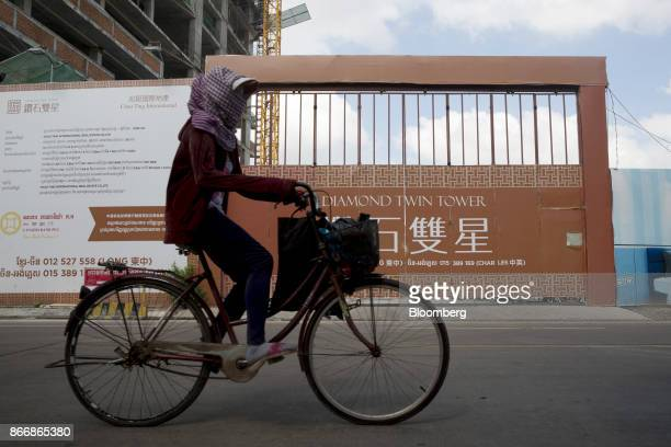 A woman rides a bicycle past the Diamond Twin Tower construction site developed by Chao Ting International Real Estate Co in Phnom Penh Cambodia on...