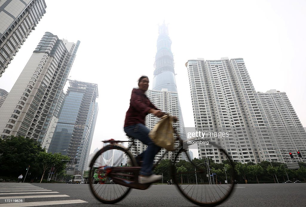 A woman rides a bicycle past the Shanghai Tower, center rear, as it stands under construction next to residential buildings in the Lujiazui district of Shanghai, China, on Sunday, June 30, 2013. China's President Xi Jinping said officials shouldn't be judged solely on their record in boosting gross domestic product, the latest signal that policy makers are prepared to tolerate slower economic expansion. Photographer: Tomohiro Ohsumi/Bloomberg via Getty Images