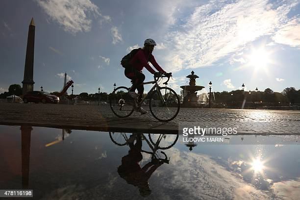 A woman rides a bicyle at sunset on June 22 2015 at Place de la Concorde in Paris AFP PHOTO / LUDOVIC MARIN