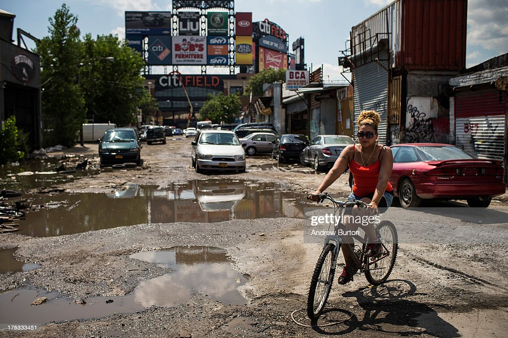 A woman rides a bike around a puddle on August 2, 2013 in the Willet's Point neighborhood of the Queens borough of New York City. The neighborhood has been in a battle with the city of New York for years, which plans to demolish the neighborhood and invest $3 billion for a mall, apartments and more parking for nearby Citi Field. Members of the neighborhood argue that over two hundred small businesses are established in the neighborhood and should not be evicted.