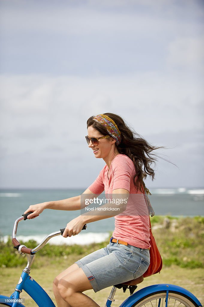A woman rides a bike by the ocean in the summer : Stock Photo