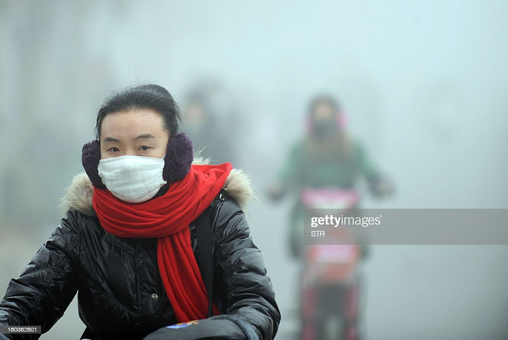 A woman rides a bike in the heavy smog with a mask on a street in Haozhou, central China's Anhui province on January 30, 2013. Across China public frustration mounted this week as dense smog blanketed swathes of the country, with even state-run media questioning the authorities' ability to meet their goal of building a 'beautiful China'. CHINA