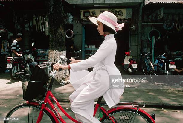 A woman rides a bike while wearing a traditional ao dai holding one end up to keep it away from the greasy bicycle chain