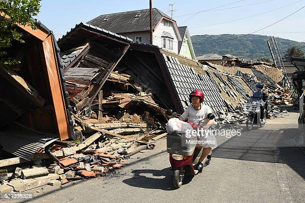 A woman rides a scooter in front of a collapsed house a day after the 2016 Kumamoto Earthquake on April 15 2016 in Mashiki Kumamoto Japan As of April...