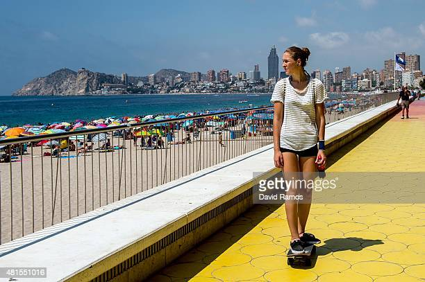 A woman rides a skateboard along the promenade at Poniente Beach on July 22 2015 in Benidorm Spain Spain has set a new record for visitors with 292...