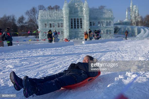 A woman rides a sleigh before the opening ceremony of the Harbin International Ice and Snow Festival in Harbin northeast China's Heilongjiang...