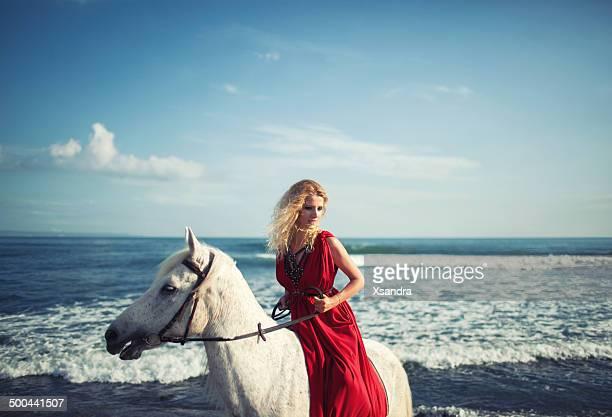 Woman rides along the beach on a horse