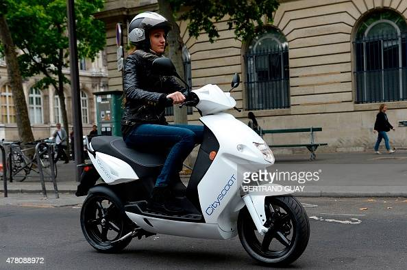 a woman rides as she presents a scooter from french cityscoot the first worldwide company to. Black Bedroom Furniture Sets. Home Design Ideas