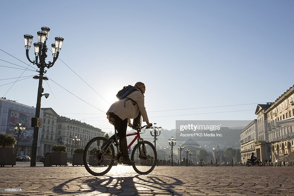 Woman rides bicycle through urban piazza, sunrise : Stock Photo