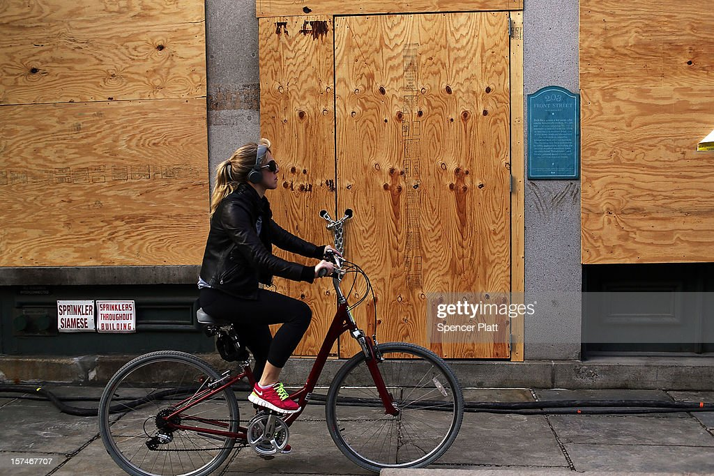A woman rides by a closed business affected by Superstorm Sandy in the heavily damaged South Street Seaport on December 3, 2012 in New York City. South street Seaport, an area popular with tourists which was about to go through a major redevelopment, suffered severe damage from Hurricane Sandy. Most of the buildings and businesses, including the South Street Seaport Museum, suffered severe flooding and remained closed. According to a new Siena Research Institute poll, most New Yorkers overwhelmingly agree that climate change was behind Hurricane Sandy.