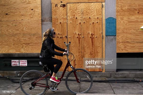 A woman rides by a closed business affected by Superstorm Sandy in the heavily damaged South Street Seaport on December 3 2012 in New York City South...