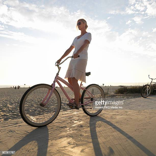 Woman rides cruiser bike along beach walkway