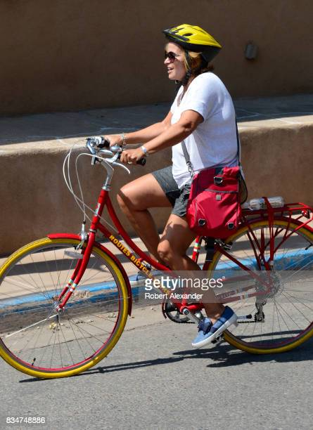 A woman rides her bicycle along Canyon Road home to dozens of art galleries in Santa Fe New Mexico
